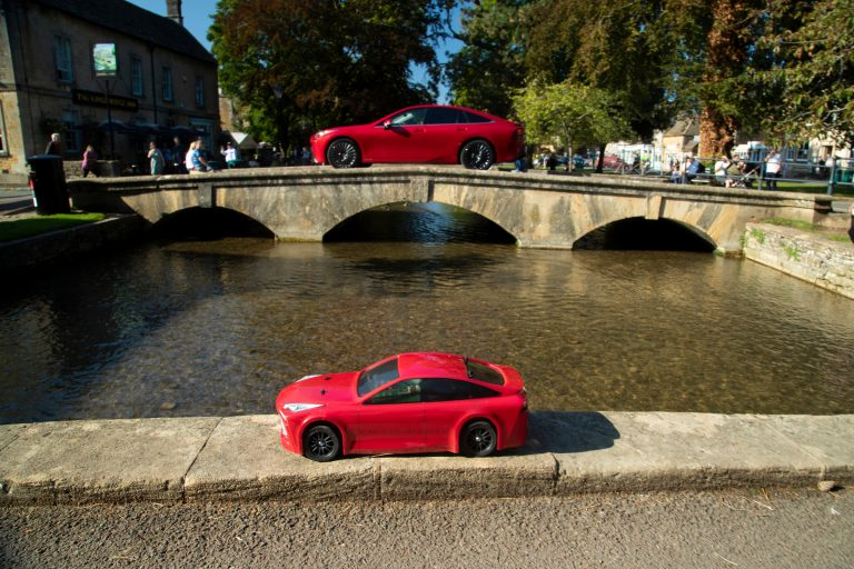 Both little and large Mirai cars, crossing bridges in Bourton-on-the-Water